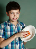 Happy preteen boy wash dishes royalty free stock photography