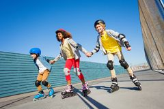 Kids holding hands while rollerblading outdoors Royalty Free Stock Photos