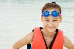 Happy preteen girl in life vest and swimming goggles against blu Stock Photos