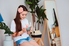 Happy preteen girl resting at home, sitting with cup of hot tea. With houseplants on backgroung in stylish modern interior Royalty Free Stock Photo