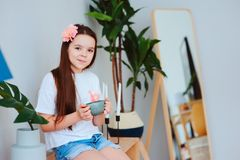 Happy preteen girl resting at home. Sitting with cup of hot tea with houseplants on background in stylish modern interior Stock Photos