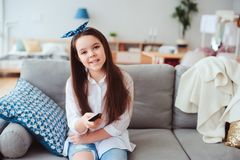 Happy preteen girl watching tv and relaxing at home on cozy couch Royalty Free Stock Photography