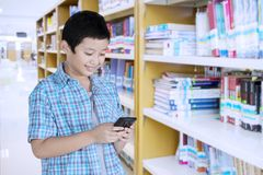 Happy preteen student using a smartphone. Image of a happy preteen student using a smartphone while standing in the library Royalty Free Stock Photography