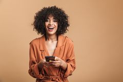Happy pretty african woman holding smartphone and looking at camera royalty free stock image
