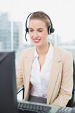 Happy pretty agent wearing headset dealing with customer Royalty Free Stock Photography