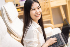 Happy pretty asian woman using laptop sitting on cosy sofa Royalty Free Stock Image