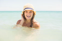 Happy pretty blonde bathing into the sea with hat Stock Photography