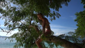 Happy pretty blonde woman wearing colourful swimwear sitting on a branch on a beautiful summer day with beautiful sea and sky back stock footage