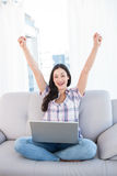 Happy pretty brunette looking at camera and using laptop Stock Image