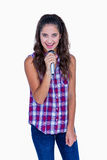 Happy pretty brunette singing on microphone Royalty Free Stock Images