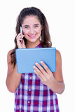 Happy pretty brunette using tablet computer and having phone call Royalty Free Stock Photos