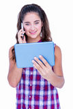 Happy pretty brunette using tablet computer and having phone call Stock Photography