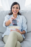 Happy pretty brunette watching tv and eating pop corn Stock Photos
