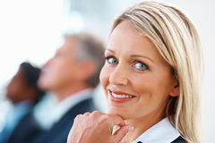 Happy pretty business woman with staff in the back Royalty Free Stock Photo