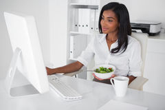 Happy pretty businesswoman eating a salad at her desk Stock Photography