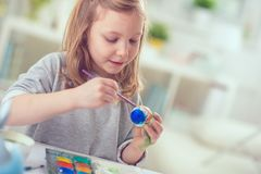 Happy pretty child girl having fun during painting eggs for east Royalty Free Stock Photo