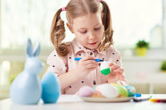 Happy pretty child girl having fun during painting eggs for east Royalty Free Stock Images