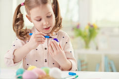 Happy pretty child girl having fun during painting eggs for east Royalty Free Stock Photos