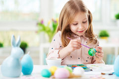 Happy pretty child girl having fun during painting eggs for east Stock Photos