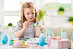 Happy pretty child girl having fun during painting eggs for east Stock Images