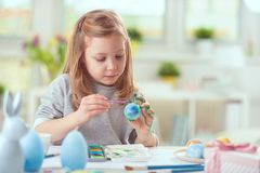 Happy pretty child girl having fun during painting eggs for east Royalty Free Stock Photography