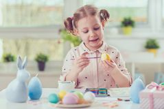 Happy pretty child girl having fun during painting eggs for east Stock Photography