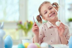 Happy pretty child girl having fun during painting eggs for east Stock Image