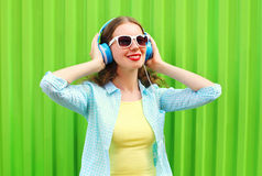 Happy pretty cool woman listens to music in headphones over green Royalty Free Stock Photos