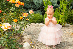 Happy pretty girl kid celebrate her birthday with rose decor in beautiful garden. Positive human emotions feelings joy. Royalty Free Stock Images