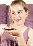 Happy pretty girl with remote control watching tv Stock Photos