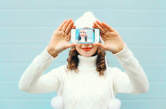 Happy pretty girl taking photo self portrait on smartphone over blue background in a winter knitted clothes. Happy pretty girl taking photo self portrait on Stock Photo