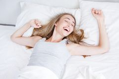 Happy, pretty girl waking up stretching arms on the bed in the morning. Rest,sleeping,people and comfort concept. royalty free stock image