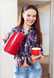 Happy pretty housewife with tea kettle and cup Royalty Free Stock Photo