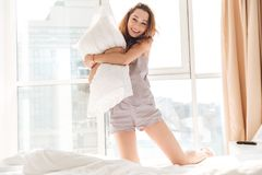 Happy pretty lady sitting on bed holding pillow Royalty Free Stock Photography