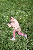 Happy pretty little girl in pink lies on green grass Royalty Free Stock Photo