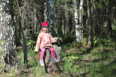 Happy pretty little girl in pink sits on tree stump Royalty Free Stock Photography