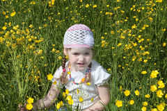 Happy pretty little girl sits among yellow flowers Royalty Free Stock Images