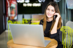 Happy pretty manager talking on mobile phone with client in modern office. Happy pretty manager talking on mobile phone with client Stock Image