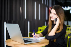 Happy pretty manager talking on mobile phone with client and write notes in modern office. Happy pretty manager talking on mobile phone with client Stock Photos