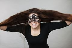 Mysterious woman wearing lace mask. Happy pretty mysterious woman wearing black eye lace mask having tousled windblown long brown hair royalty free stock photo