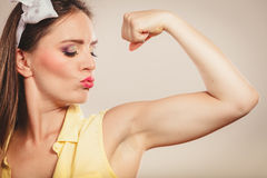 Happy pretty pin up girl showing off muscles. Royalty Free Stock Photography