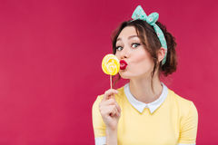 Happy pretty pinup girl eating and kissing yellow lollipop. Over pink background stock photos