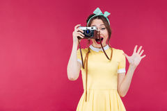 Happy pretty pinup girl taking pictures with vintage camera Royalty Free Stock Image