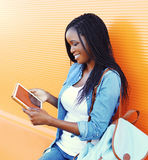 Happy pretty smiling african woman using tablet pc Royalty Free Stock Image