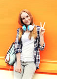 Happy pretty smiling girl with headphones listens to music. Having fun in city Stock Photography
