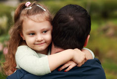 Happy pretty smiling kid girl hugging her father with love outdo Stock Photos