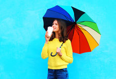 Happy pretty smiling woman with coffee cup and colorful umbrella in autumn day looking up over colorful blue background Stock Image
