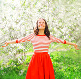 Happy pretty smiling woman enjoying smell flowers over spring stock photos