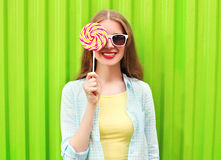 Happy pretty smiling woman and lollipop over colorful green. Portrait happy pretty smiling woman and lollipop over colorful green background Royalty Free Stock Photos