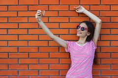 Happy pretty smiling woman makes self-portrait on smartphone over colorful red brick background stock photography